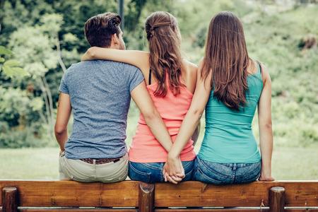 Triángulo de amor, una niña está abrazando un chico y él es la mano con otra chica, que están sentados juntos en un banco Foto de archivo