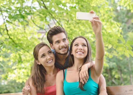 uomini belli: Cheerful smiling teens at the park sitting on a bench and taking selfies using a smart phone