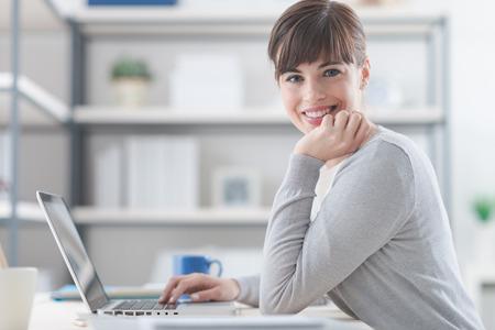 Gelukkige zekere onderneemsterzitting bij bureau en het werken met laptop, glimlacht zij bij camera Stockfoto