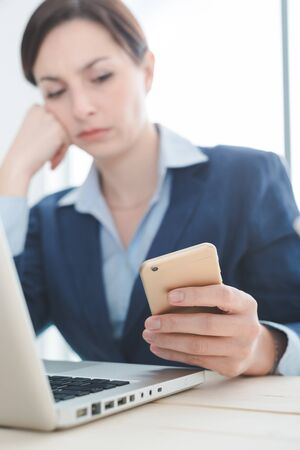concern: Pensive businesswoman working at office desk and reading sms on her mobile phone