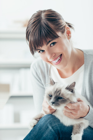smiling cat: Young woman smiling at camera and caressing her beautiful birman cat on her legs