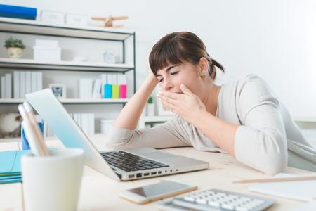 Slaperige jonge zakenvrouw zittend aan een bureau, werken met een laptop en geeuwen