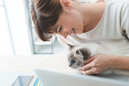 a lovely cat: Young woman sitting at desk and cuddling her lovely cat, togetherness and pets concept