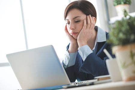 Depresso imprenditrice annoiato che lavora alla scrivania in ufficio e in rete con un computer portatile, noioso concetto di lavoro