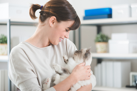 affectionate: Young woman at home holding her beautiful cat in her arms, home interior on background, pets and lifestyle concept