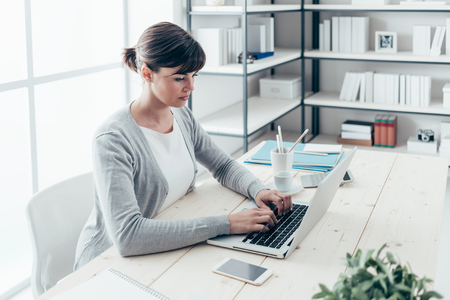 professional woman: Confident young freelancer sitting at office desk and working with a laptop, efficiency and entrepreneurship concept