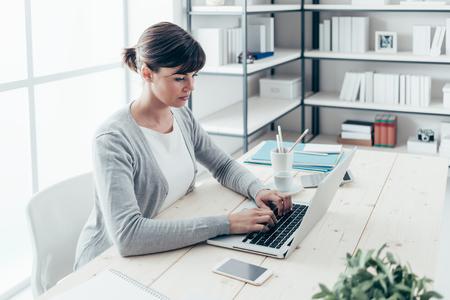jeune pigiste Confiant assis au bureau et en travaillant avec un ordinateur portable, l'efficacité et le concept de l'esprit d'entreprise
