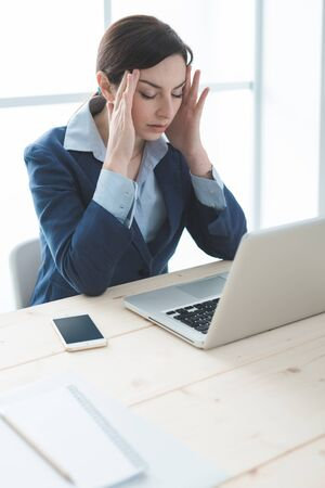 overwork: Exhausted businesswoman in her office with head in hands, she is having a bad headache, overwork and stress concept