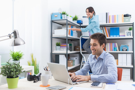 tidying up: Two people working in the office, the man is working with a laptop on foreground, the woman is standing on a ladder and tidying up