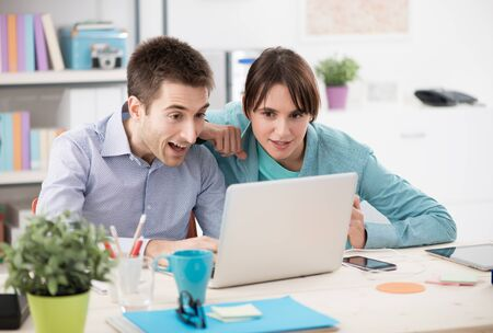 gasping: Couple at home using a laptop enjoying internet services, he is gasping and staring at monitor Stock Photo