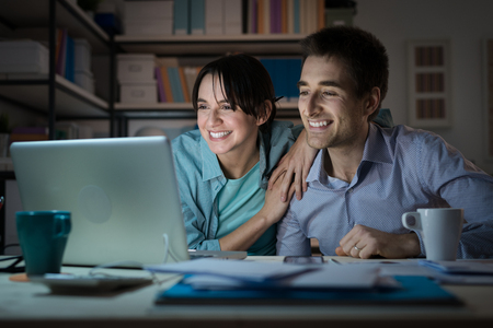 Happy smiling married couple at home using a laptop, connecting to internet and networking, communication and internet concept Stockfoto