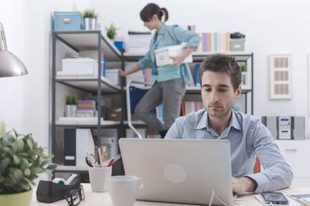 laptop home: Two people working in the office, the man is working with a laptop on foreground, the woman is standing on a ladder and tidying up