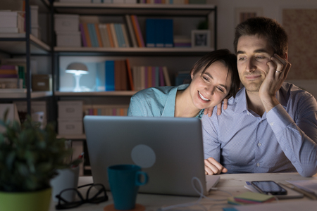 viewing: Happy loving couple at home, sitting at desk and using a laptop they are watching videos online and networking, she is leaning on her husbands shoulder