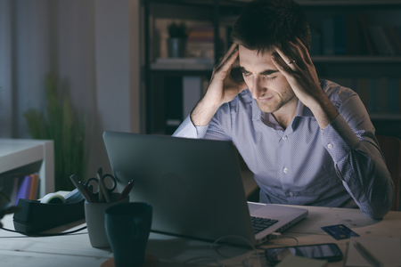 Businessman in the office working late at night and having a bad headache, overwork and stress concept Stockfoto