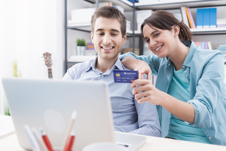 web shopping: Happy young couple at home surfing the web with a laptop and online shopping, she is holding a credit card, payments and transactions concept Stock Photo