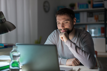 happy work: Young smiling man with hand on chin connecting to internet and using a laptop late at night, he is sitting at office desk Stock Photo