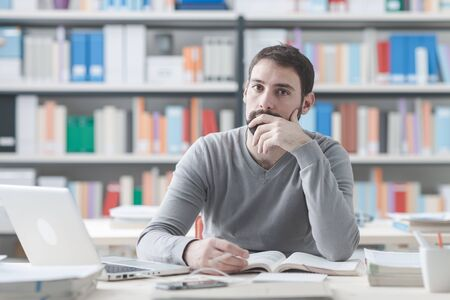man with laptop: Young man sitting at office desk and studying a manual, he is looking at camera Stock Photo