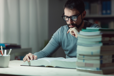 adult student: Confident adult student at the library late at night, he is sitting at desk and reading a book with hand on chin, learning and education concept Stock Photo