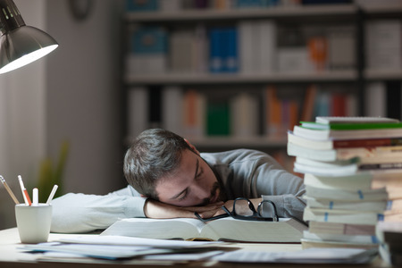 exhaustion: Young man sleeping at his desk late at night, he is leaning on a book and holding glasses, stress and exhaustion concept