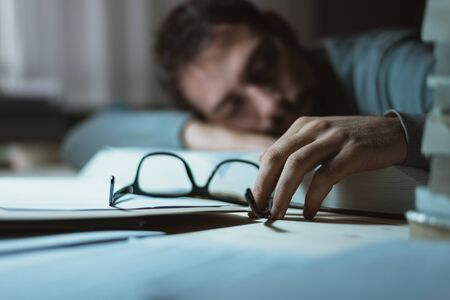 man at work: Young man sleeping at his desk late at night, he is leaning on a book and holding glasses, stress and exhaustion concept