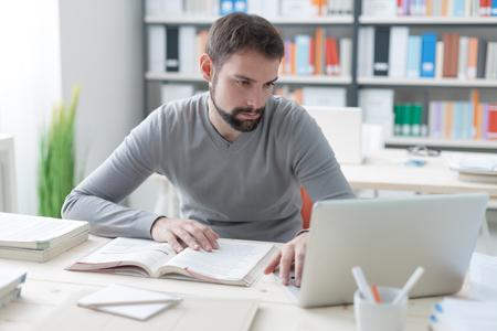 若いハンサムな男事務所の机に座って、勉強本とラップトップを使用してインターネットに接続します。