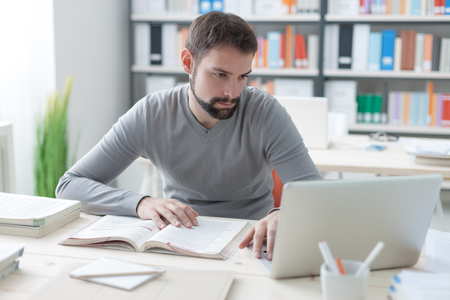 Jonge knappe man zit op kantoor bureau, het bestuderen van een boek en het verbinden met internet met behulp van een laptop Stockfoto