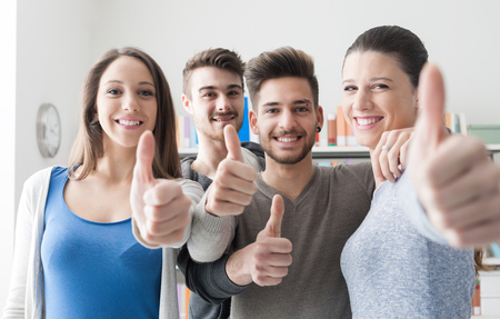 Cheerful group of students smiling at camera with thumbs up, success and learning concept