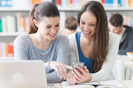 Young female students sitting at desk and studying together, they are smiling a using a smart phone