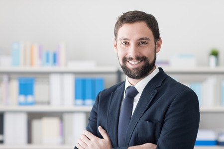 working attire: Confident young businessman posing in his office and smiling at camera, determination and professionalism concept Stock Photo