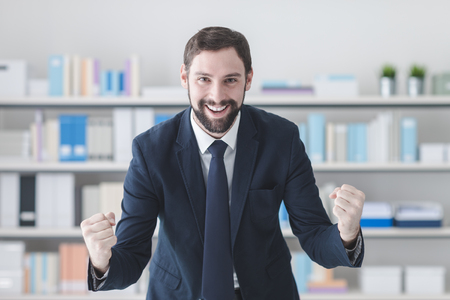 Cheerful successful businessman smiling in his office with raised fists, winning and enthusiasm concept Stock Photo