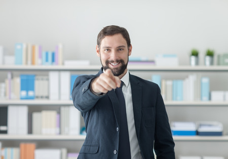 Smiling confident businessman in the office pointing at camera, selection and recruitment concept