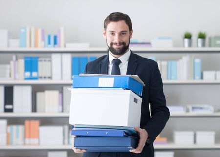 relocating: Smiling businessman carrying a box and a pile of folders, organization and efficiency concept