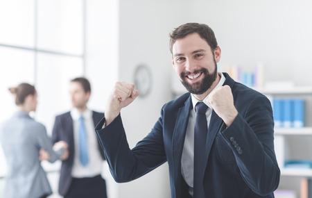 recursos humanos: Alegre joven empresario especial regocijo con los puños levantados, la satisfacción y el concepto de éxito