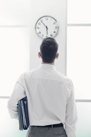 office time: Businessman in the office staring at the clock, back view, time slave and stress concept