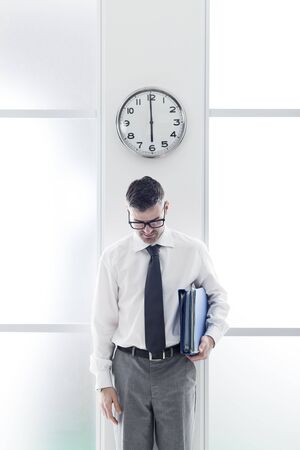 office slave: Frustrated businessman in the office standing under a clock, punctuality and time slave concept Stock Photo
