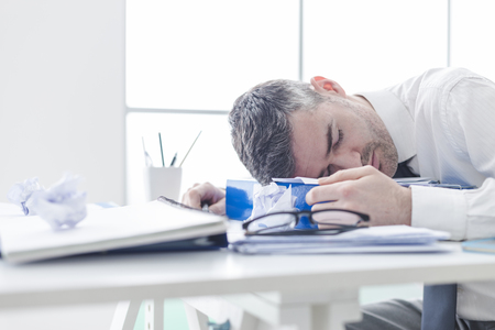 inefficient: Tired exhausted businessman overloaded with paperwork, he sleeping on his desk, stressful job concept