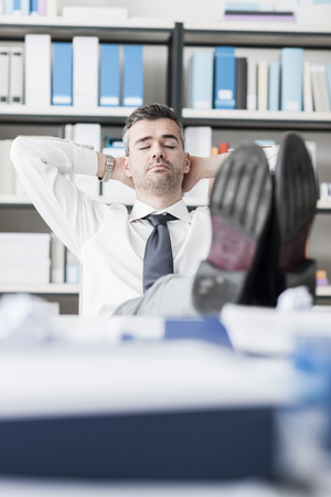 feet up: Lazy businessman sleeping in the office with his feet up on the desk and hands behind head