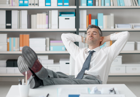inefficient: Lazy businessman sleeping in the office with his feet up on the desk and hands behind head