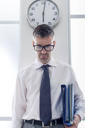 puntualidad: Hombre de negocios frustrado en la oficina de pie bajo un concepto de reloj esclavo, la puntualidad y la hora Foto de archivo