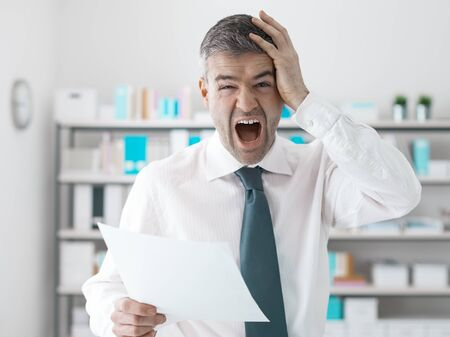 gasping: Businessman in the office receiving shocking bills and tax documents, he is gasping and screaming Stock Photo