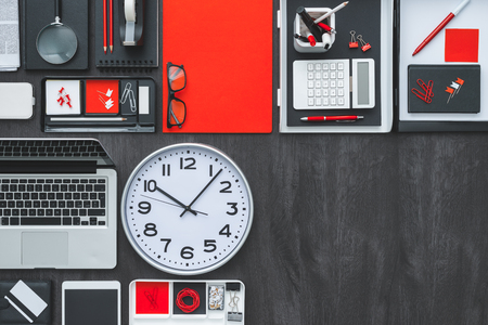 desk tidy: Corporate business desktop with laptop, office accessories and a clock: business productivity and deadlines concept