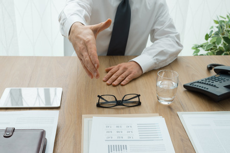 ejecutivo en oficina: Reunión de negocios en la oficina, un ejecutivo está dando un apretón de manos para el cliente, el punto de vista de tiro Foto de archivo