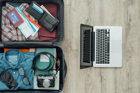 luggage travel: Open travelers bag on a desktop with clothing, accessories, credit card, tickets and passport, travel and vacations concept Stock Photo