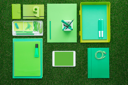 business supplies: Green office supplies and digital touch screen tablet on the grass, business and ecology concept Stock Photo