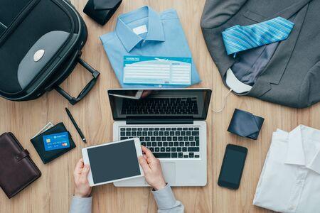 Der Unternehmensgeschäftsmann, der seine Tasche verpackt und eine Geschäftsreise plant, er bestellt Flüge online unter Verwendung eines digitalen Tablette-, Reise- und Technologiekonzeptes