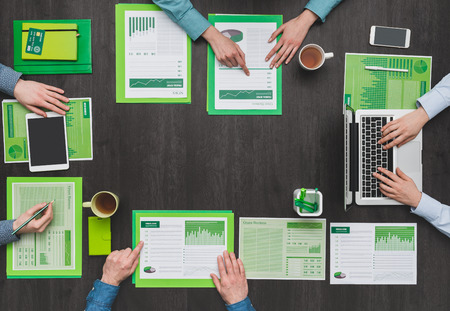 financial reports: Business team working at desk and examining green financial reports, eco business, ecology and finance concept