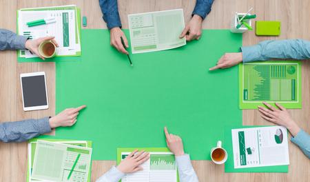 Gente di affari che lavora insieme su un desktop verde e che indica al centro, all'ambiente, al concetto verde di affari e di finanza