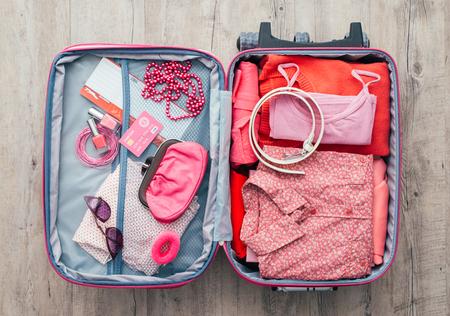 의류 및 액세서리와 함께 바탕 화면에 여자의 열린 가방, 그녀는 포장 하 고 떠날 준비, 여행 및 휴가 개념
