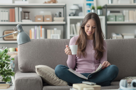 Beautiful girl at home sitting on the couch, reading a magazine and having a coffee break, relaxation concept