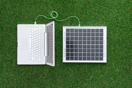 electrical energy: Laptop on the grass connected to a solar panel, alternative energy sources and electrical power generation concept